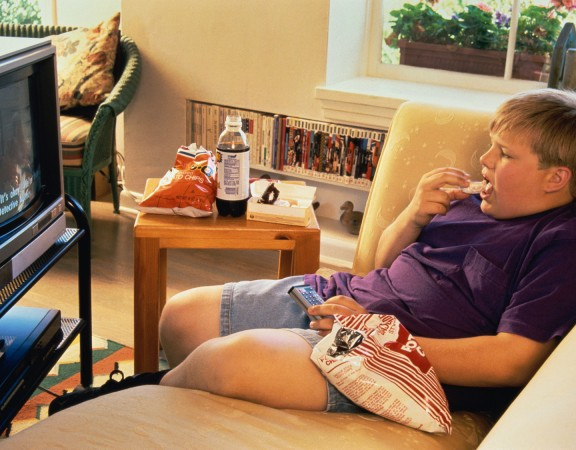 Boy (10-11) eating junk food while watching televisiongett images stock